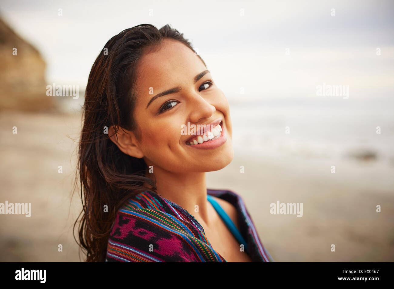 Portrait of smiling young woman wrapped in towel on beach, San Diego, California, USA Stock Photo