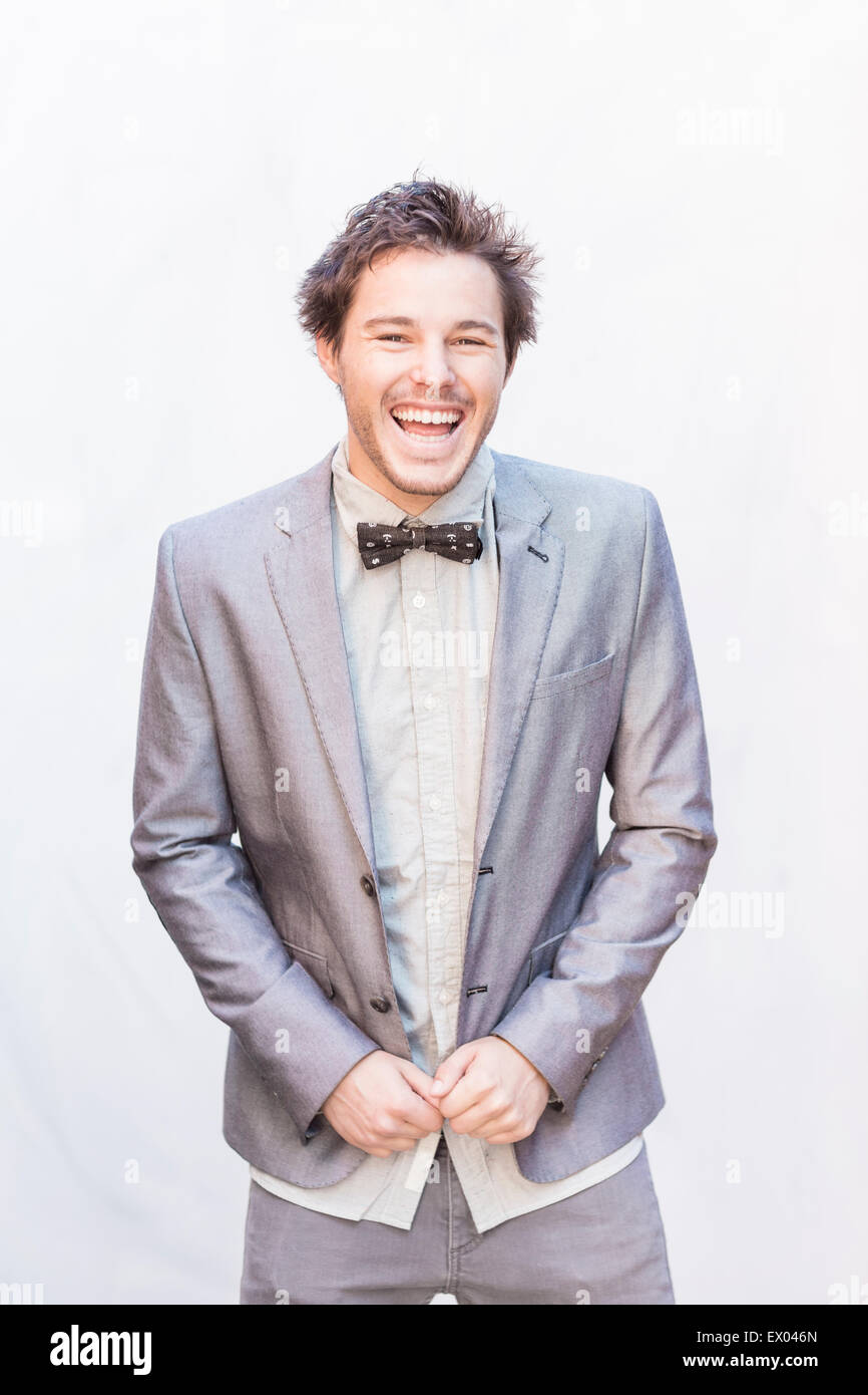 Portrait of young man wearing silver suit jacket and bow tie - Stock Image