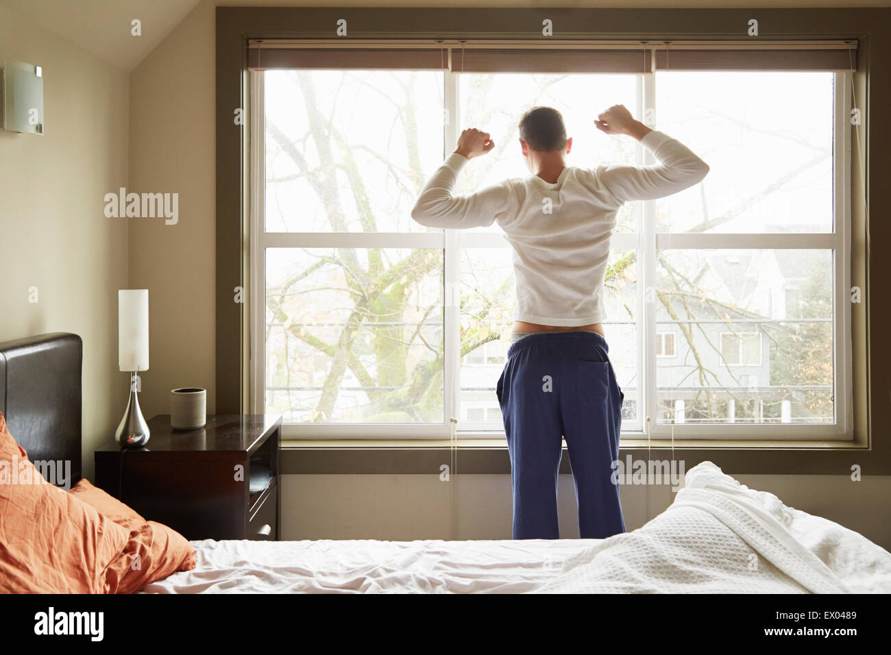 Rear View Of Young Man Stretching In Front Of Bedroom Window Stock Photo Alamy