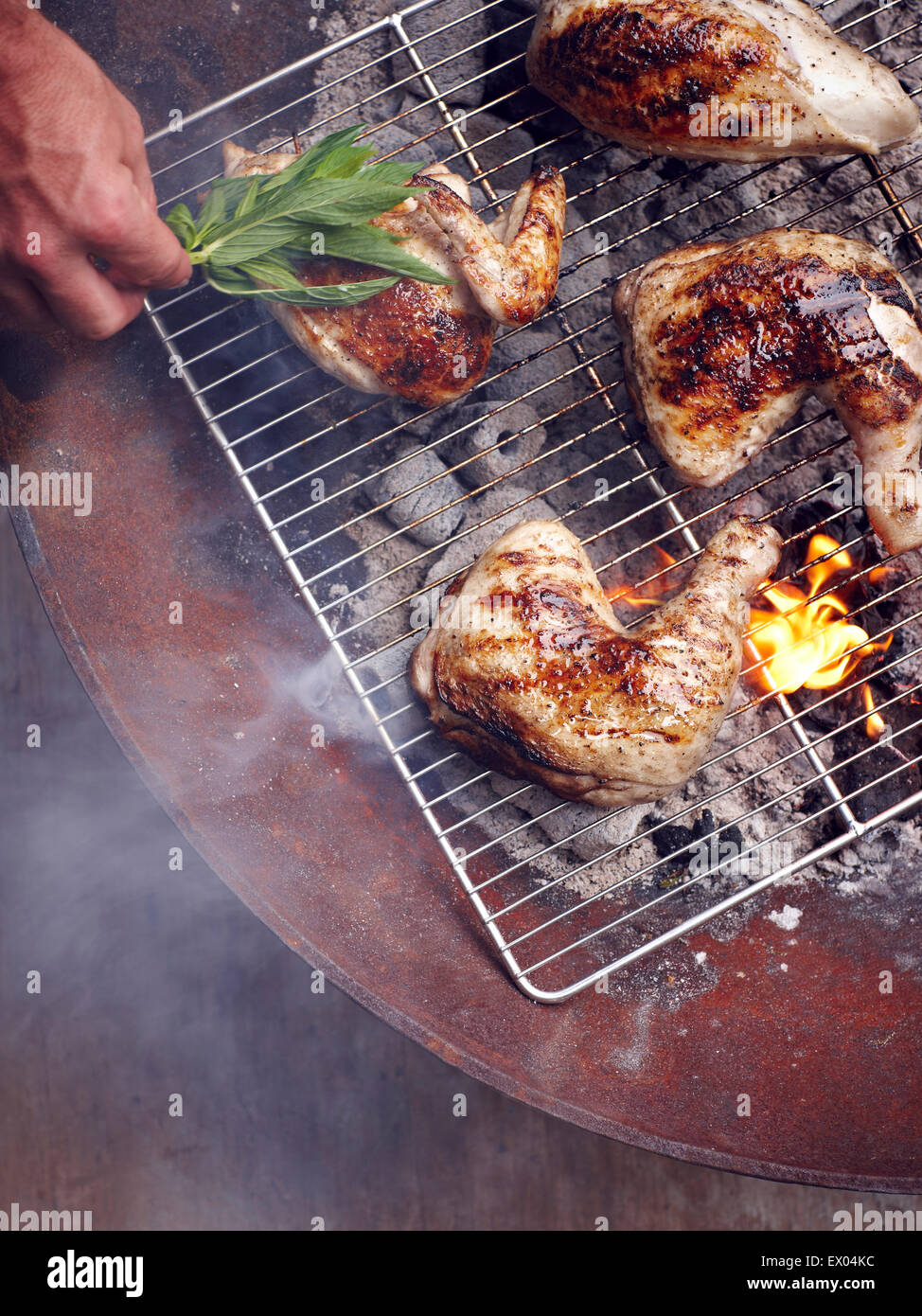 Mans hand grilling Guam chicken legs on barbecue - Stock Image