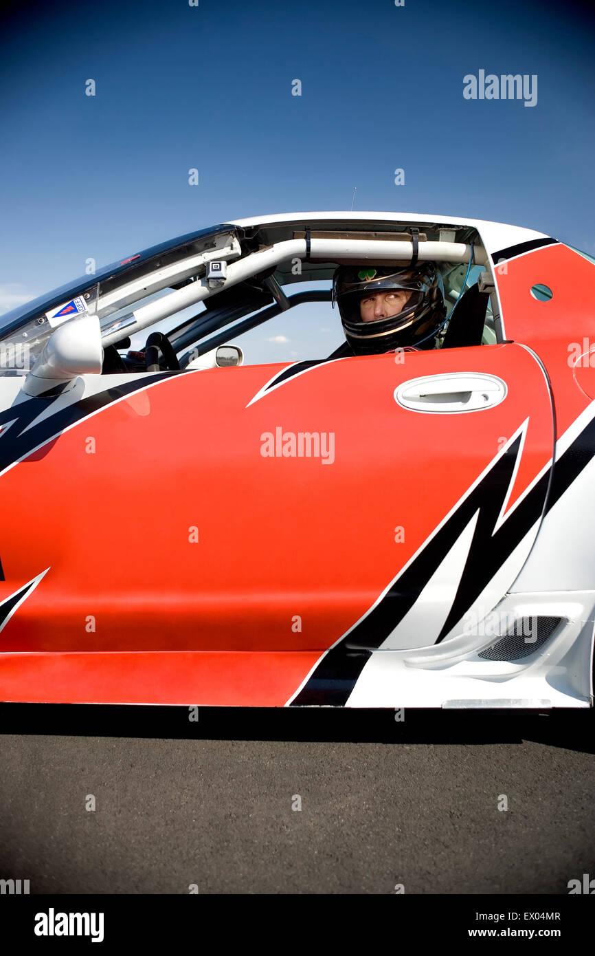 Portrait of racing car driver in racing car - Stock Image