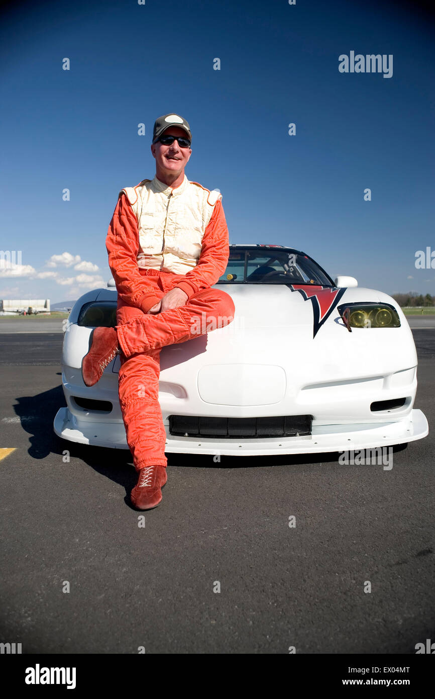 Portrait of mature male racing car driver leaning against racing car - Stock Image