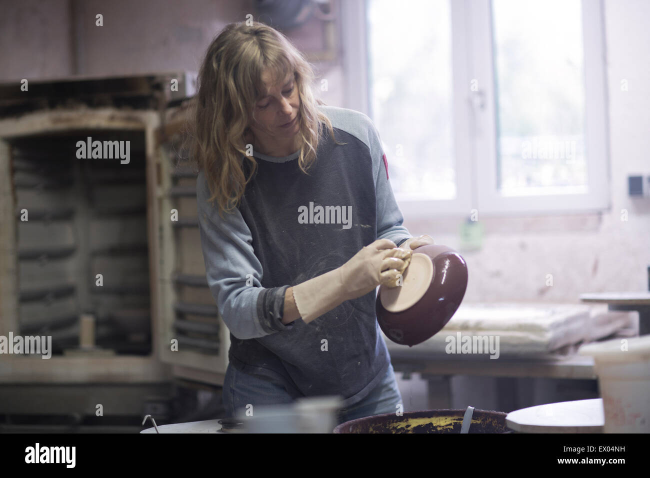 Female potter checking edge of glazed bowl in workshop - Stock Image