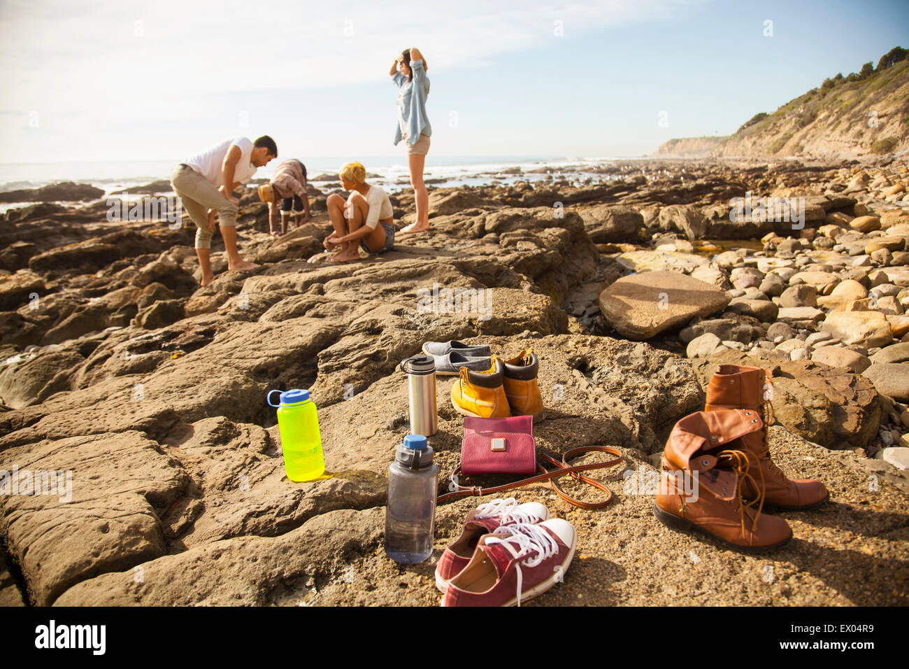Group of friends exploring rock pools on beach, shoes and belongings in foreground - Stock Image
