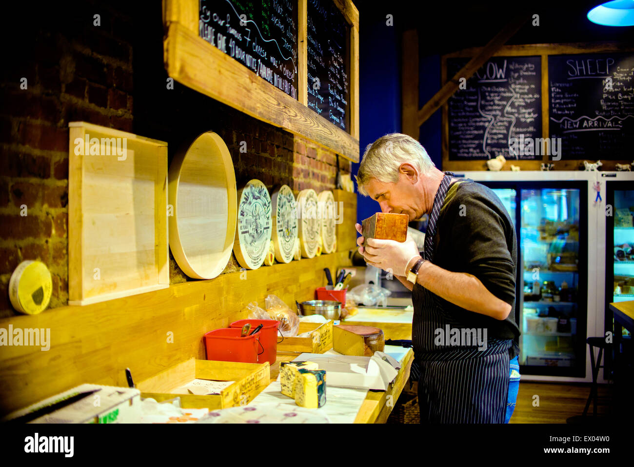 Cheesemonger smelling cheese - Stock Image