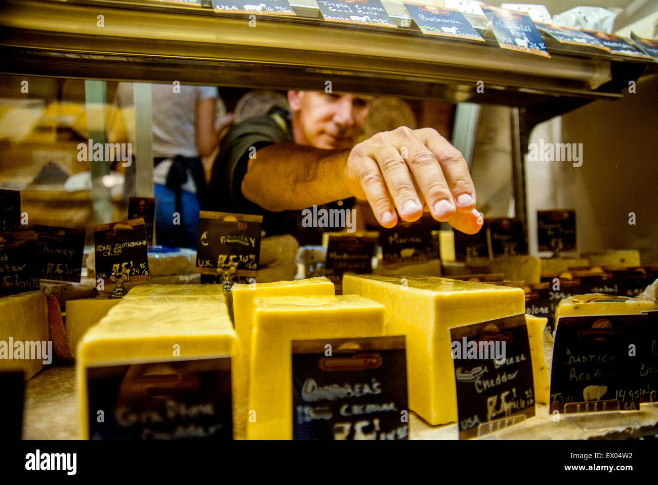 Cheesemonger reaching for cheese in display - Stock Image