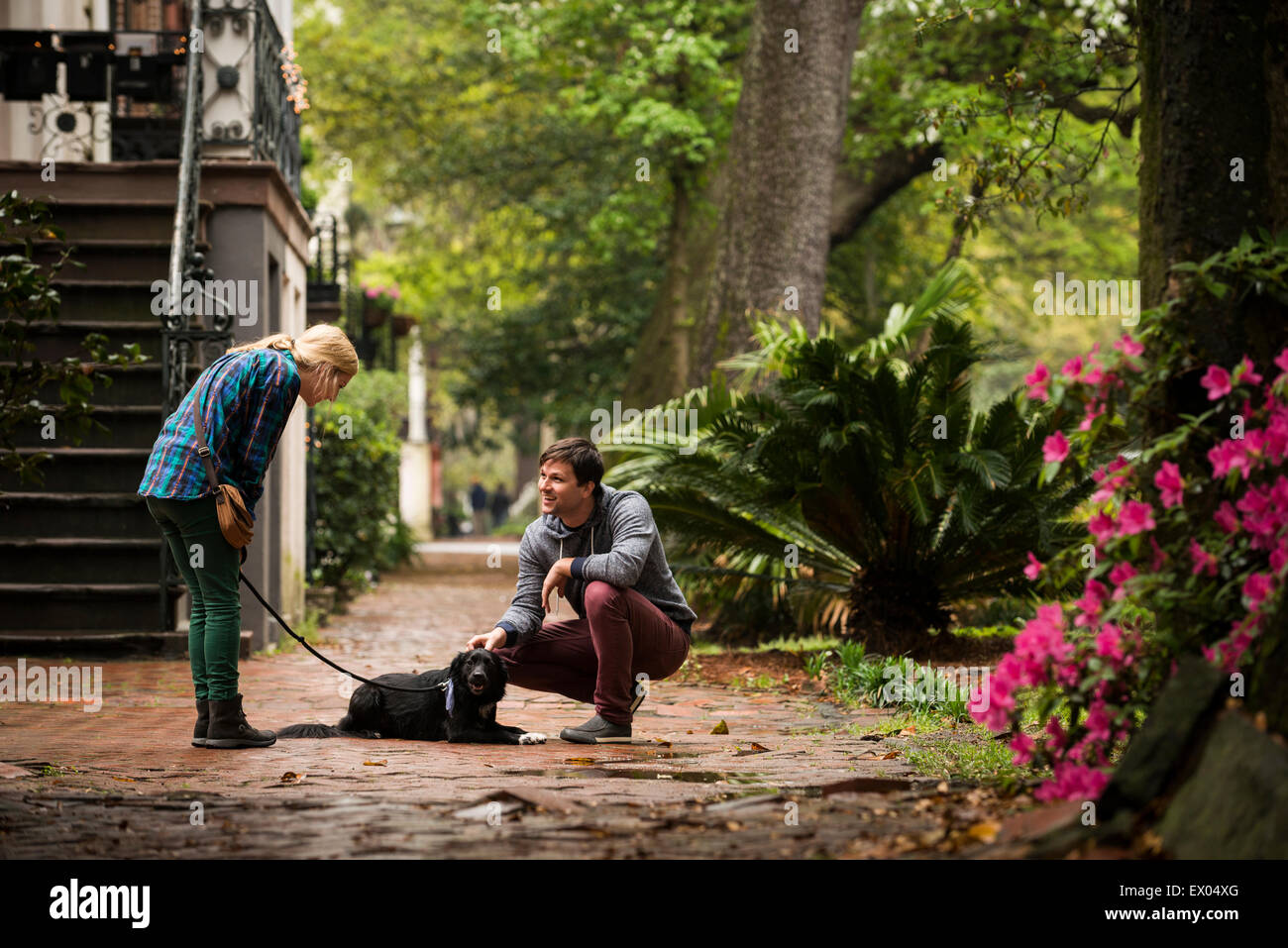Couple with dog behind house, Savannah, Georgia, USA - Stock Image