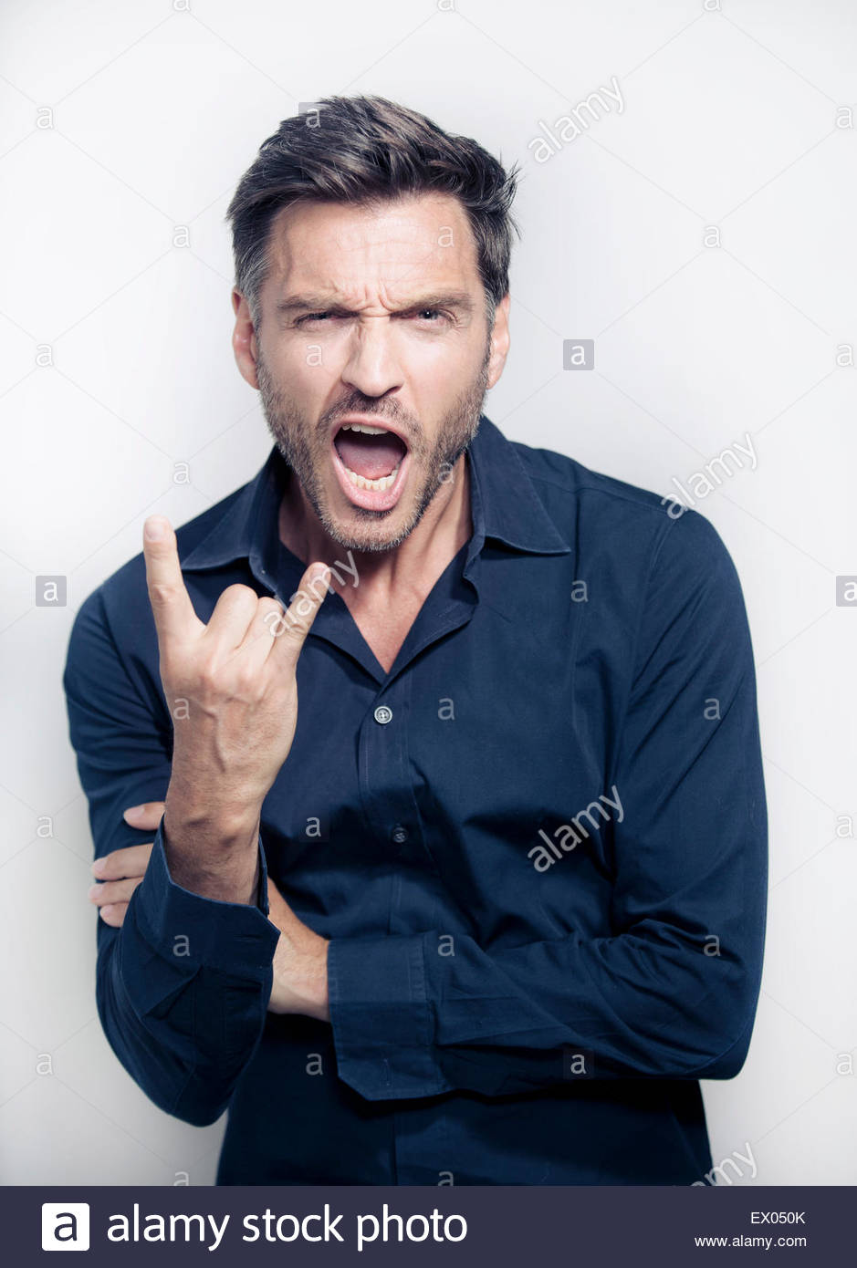 Portrait of mature man making rock and roll sign - Stock Image