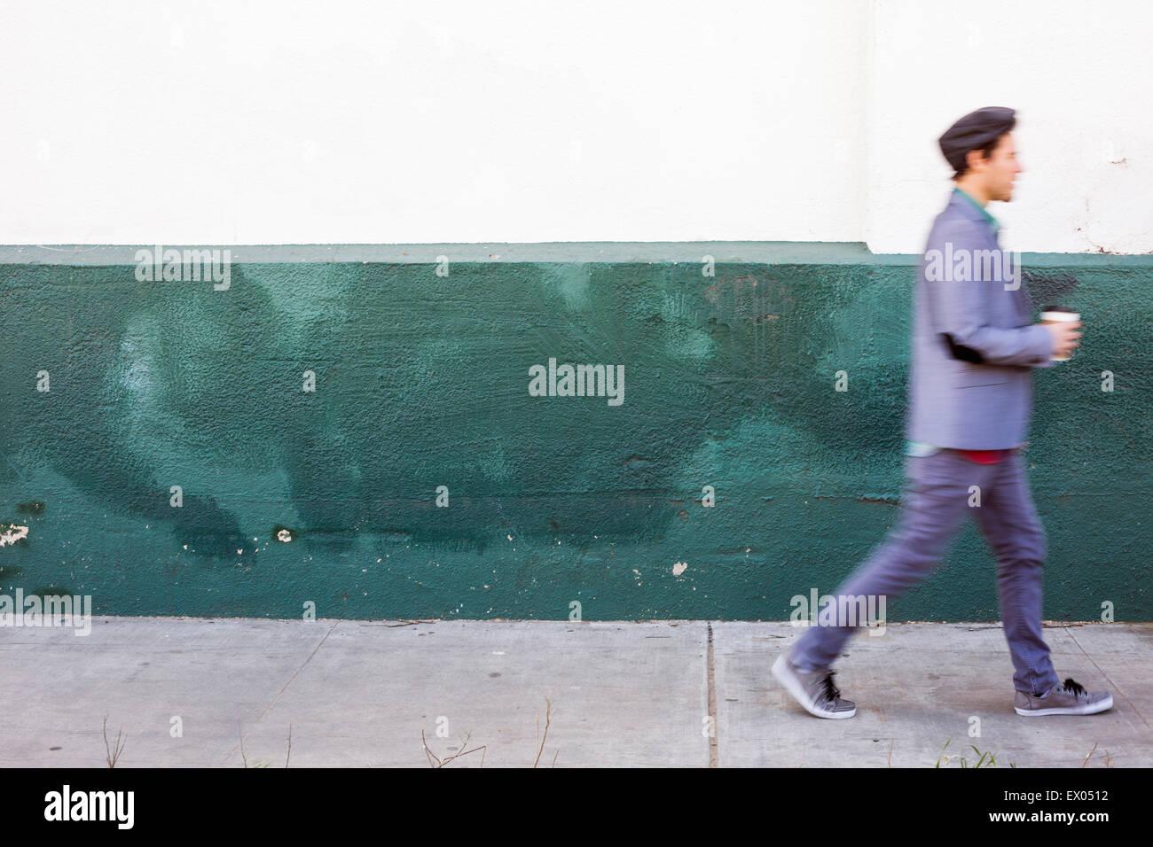 Young man walking past wall - Stock Image