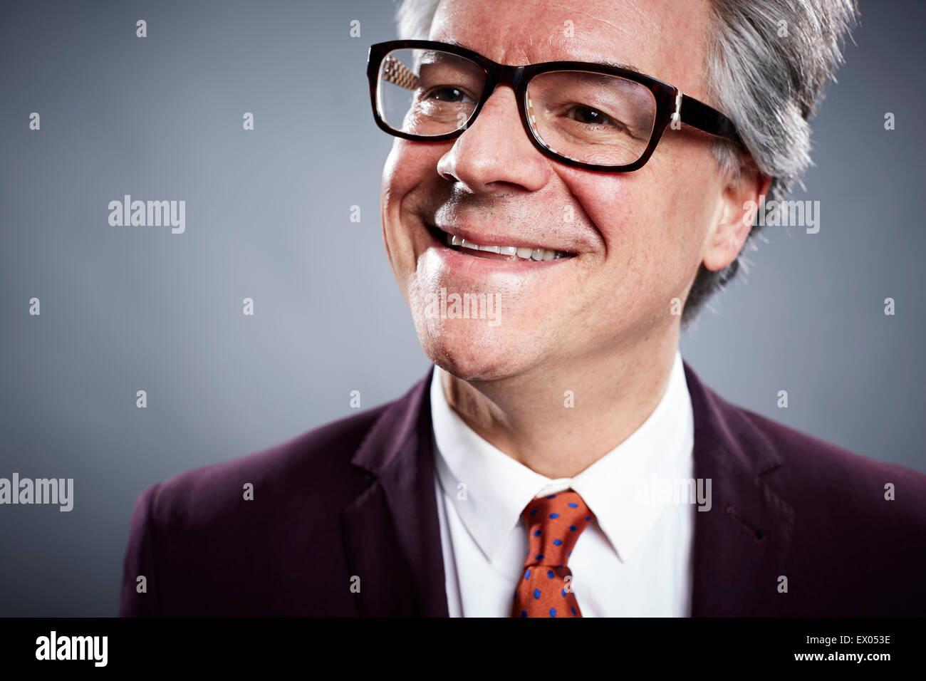 Close up studio portrait of smiling mature businessman - Stock Image