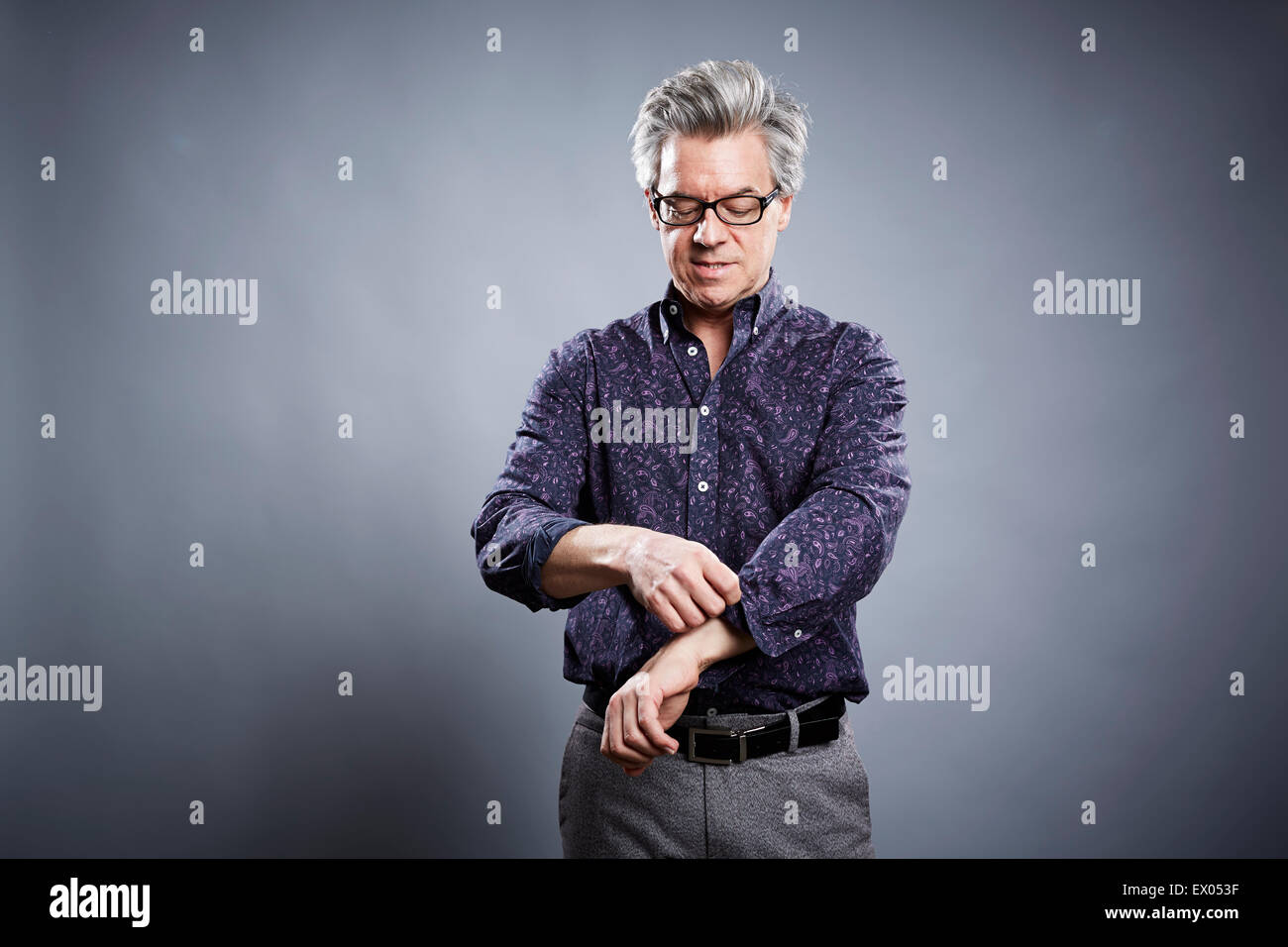 Studio portrait of mature businessman rolling up his sleeves - Stock Image