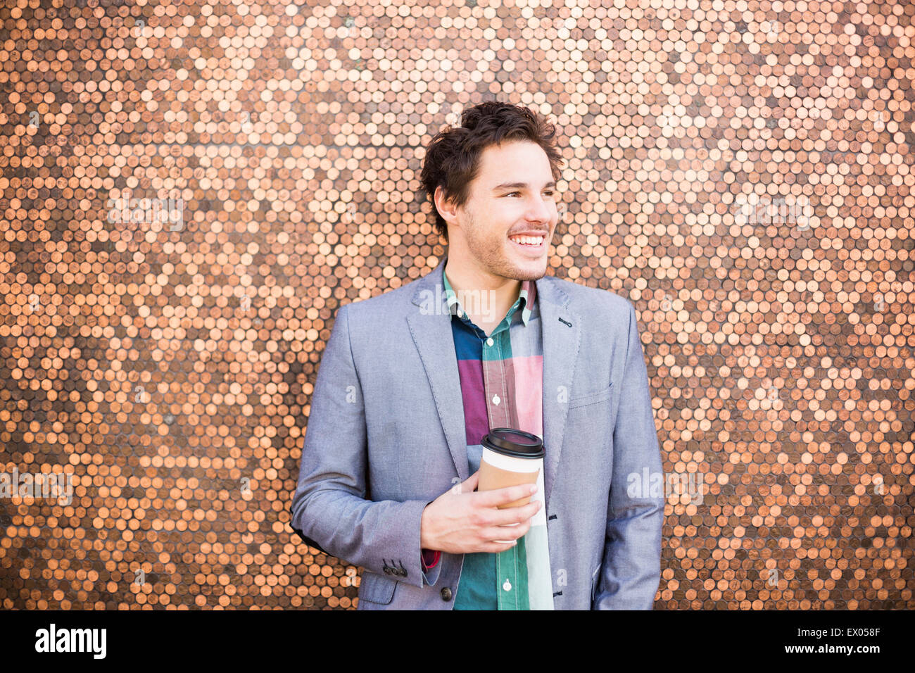 Young man by wall covered in coins - Stock Image