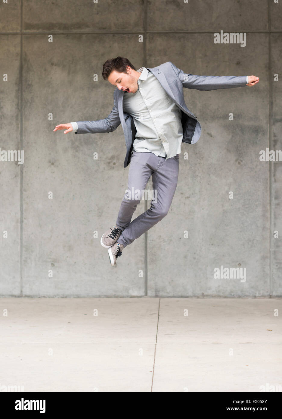 Businessman jumping mid air - Stock Image