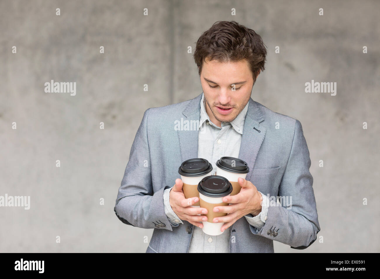 Businessman holding disposable coffee cups - Stock Image