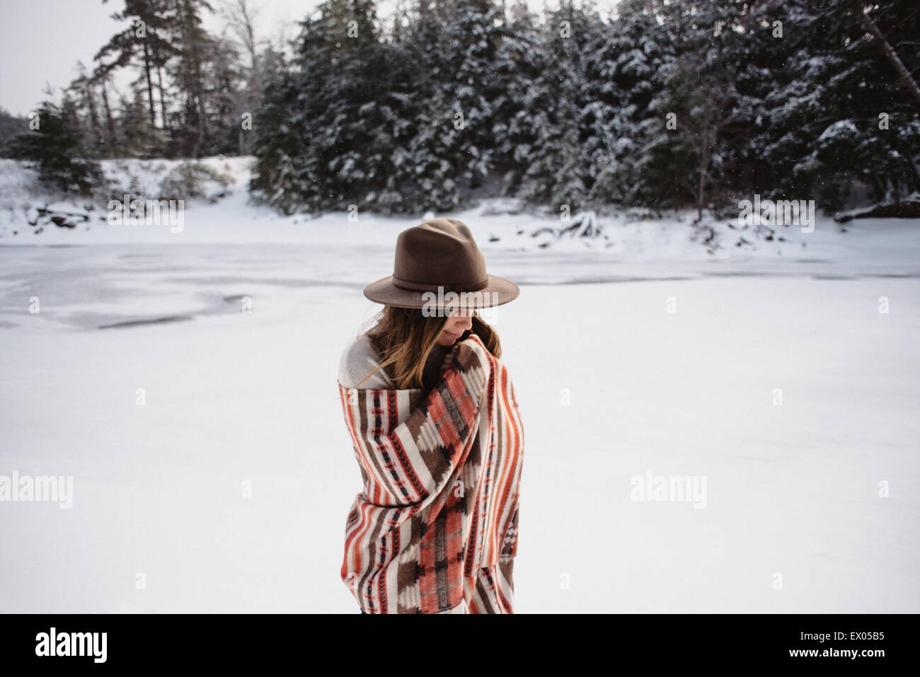 Portrait of woman wrapped in blanket in snow covered landscape, Omemee Ontario Canada - Stock Image