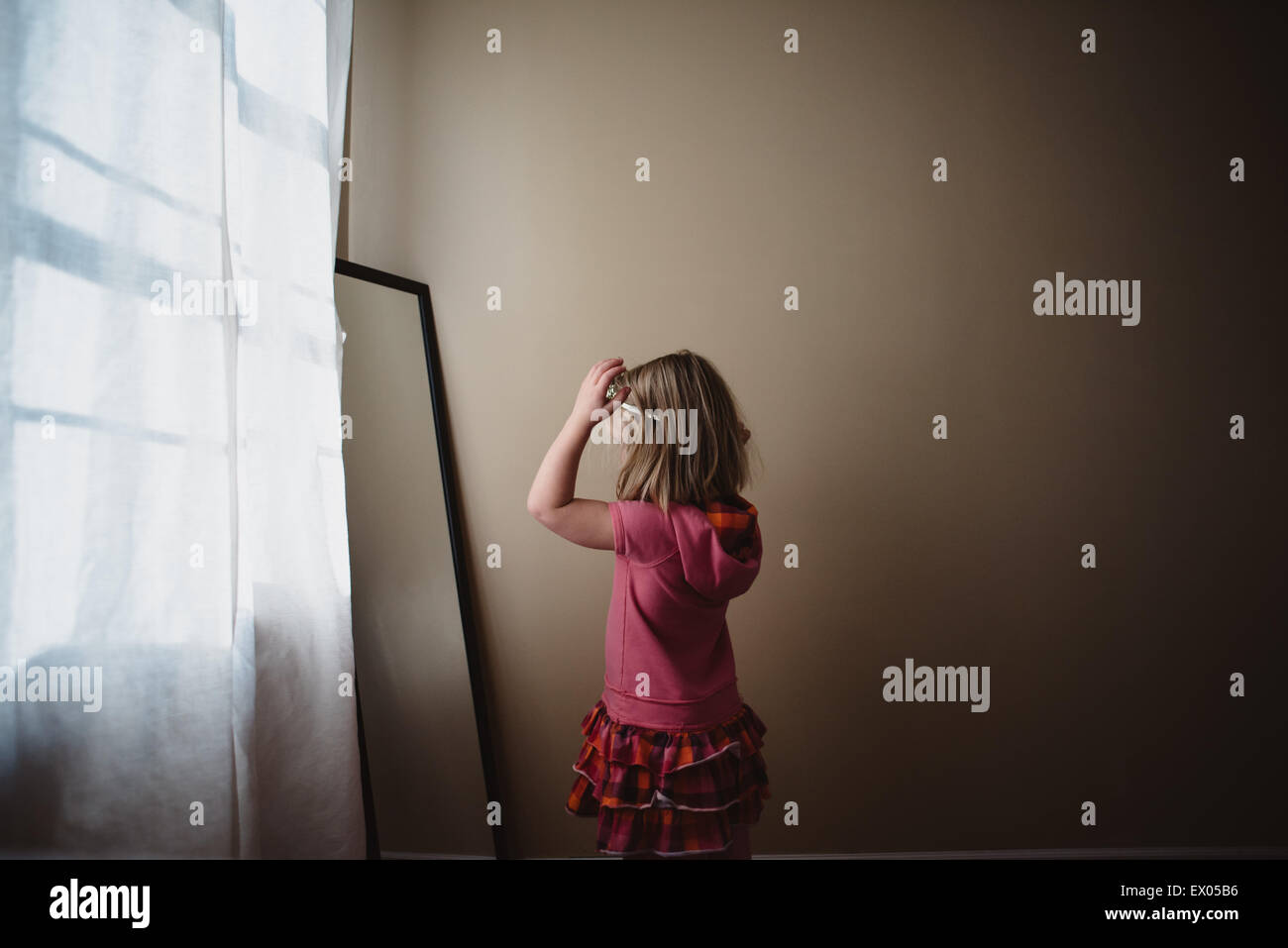 Young girl adjusting hairband in bedroom mirror - Stock Image
