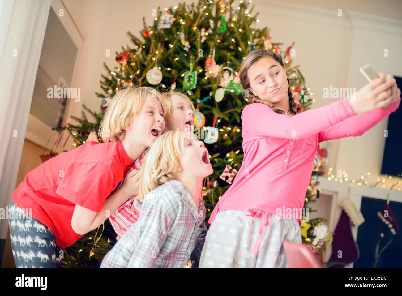 Teenage girl and brothers taking smartphone selfie at christmas - Stock Image