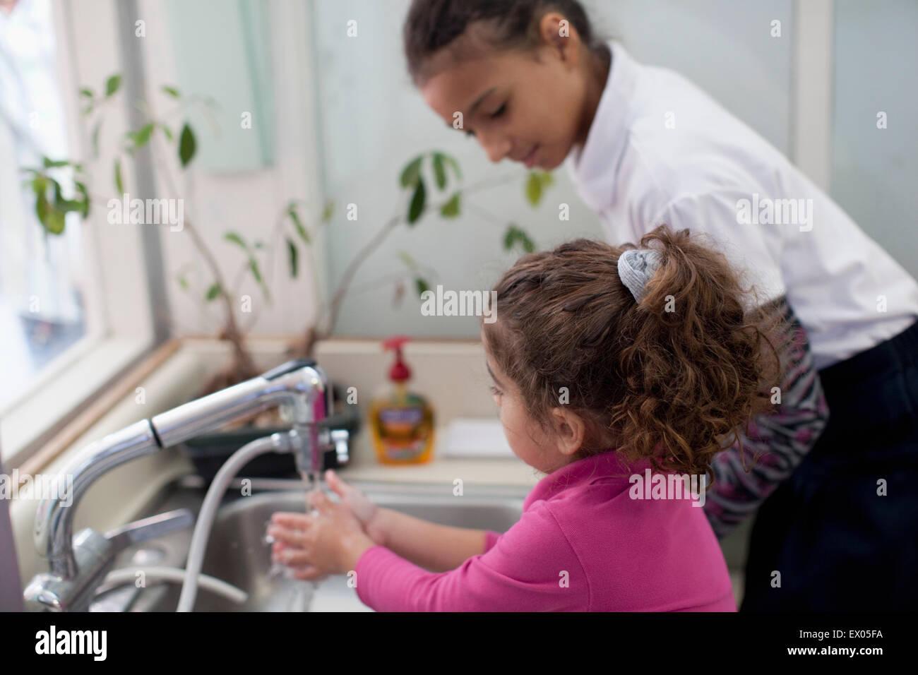 Girl watching toddler washing hands - Stock Image