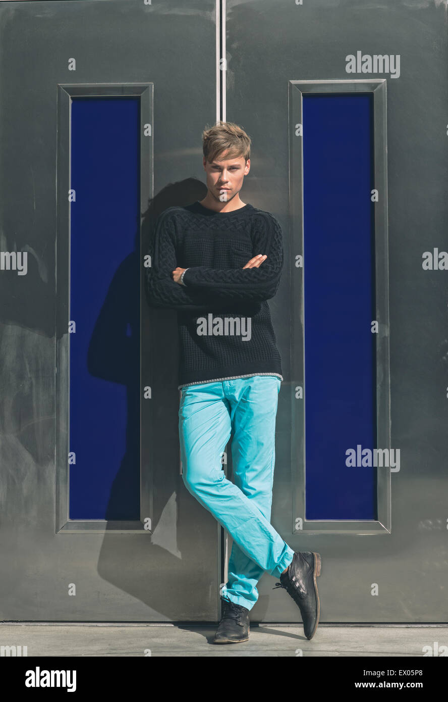 A Handsome Man Male Model Posing Outdoor Against Modern Silver Door With His Arms And Legs Crossed Winter Mens Fashion Editorial Concept