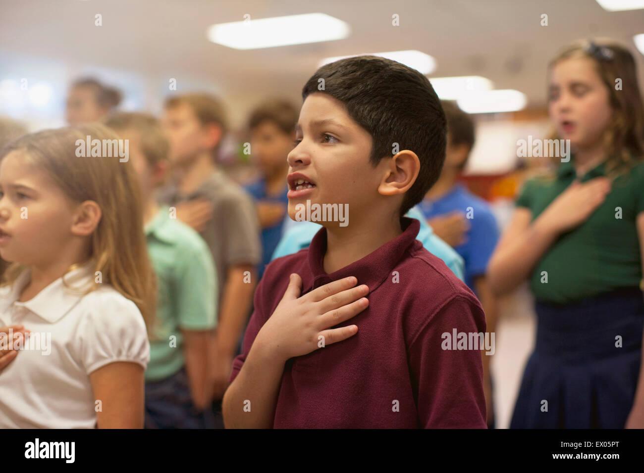 Children reciting Pledge of Allegiance in school - Stock Image