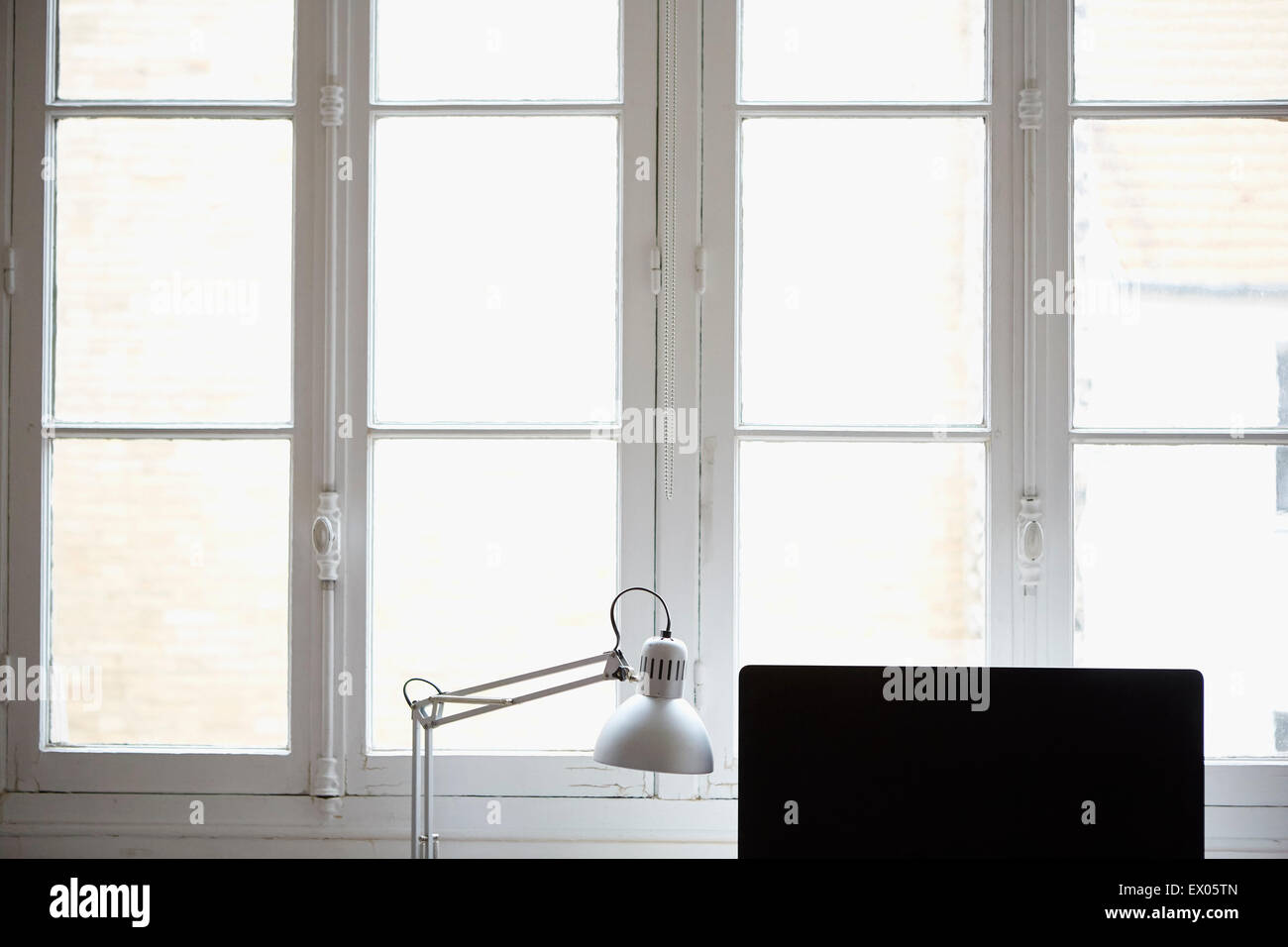 Computer monitor and desk lamp by window - Stock Image