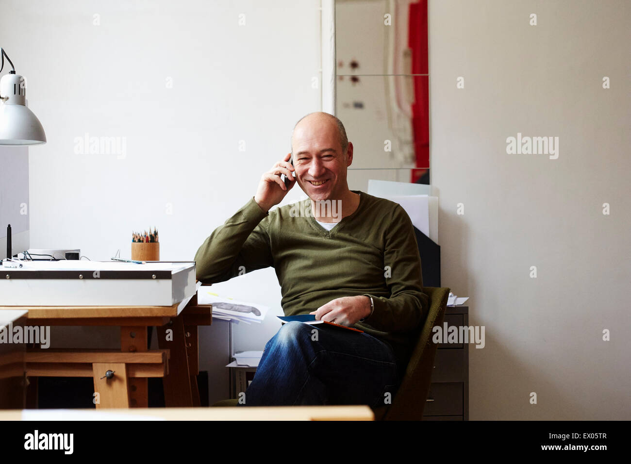 Mature man on the phone in creative studio Stock Photo