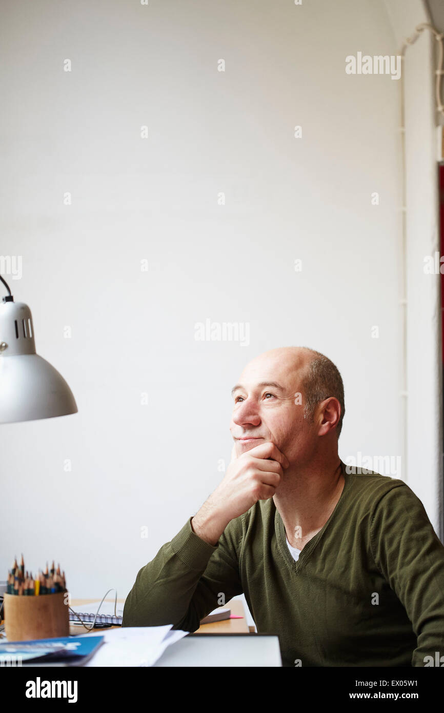 Mature man at desk with hand on chin - Stock Image