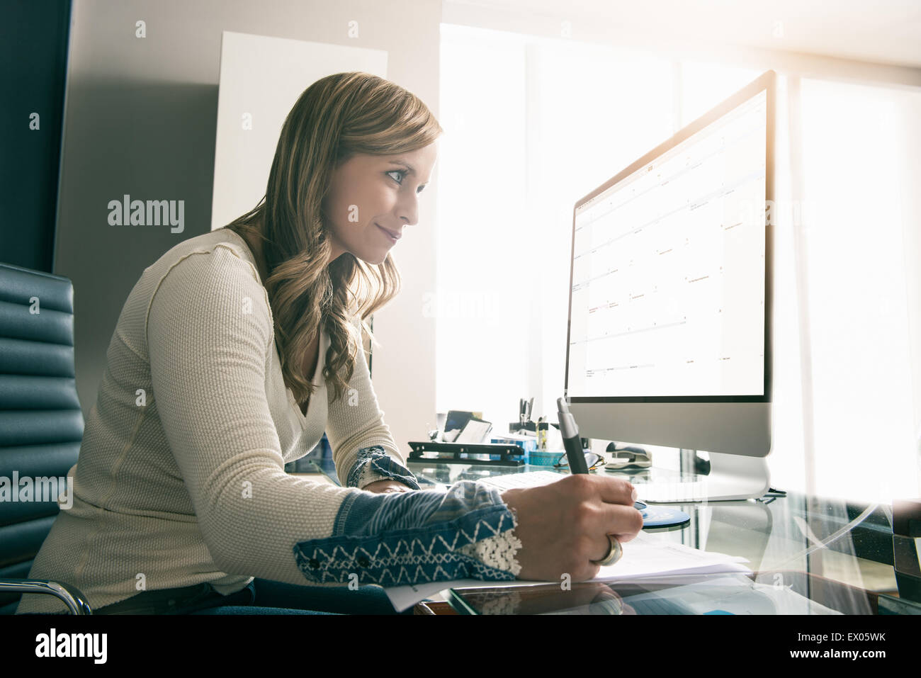 Young businesswoman using reading computer screen whilst making notes - Stock Image