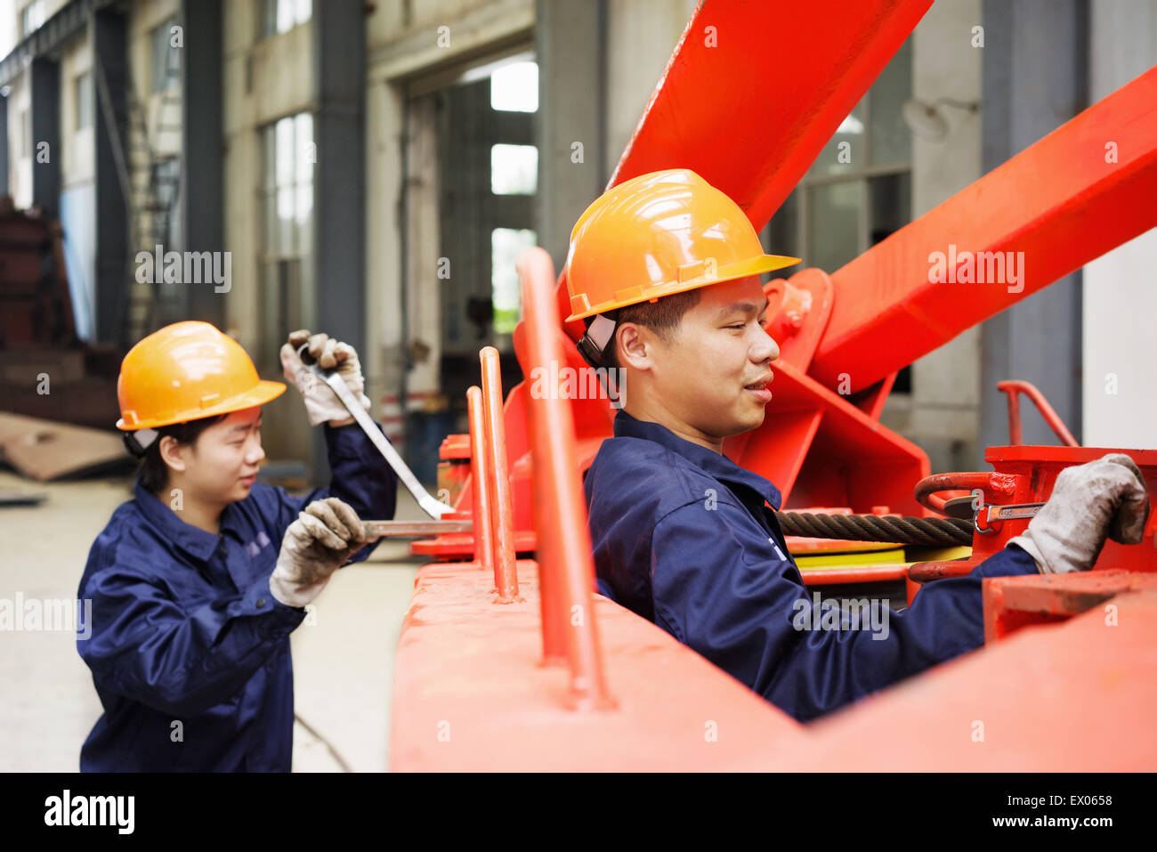 Workers using equipment in crane manufacturing facility