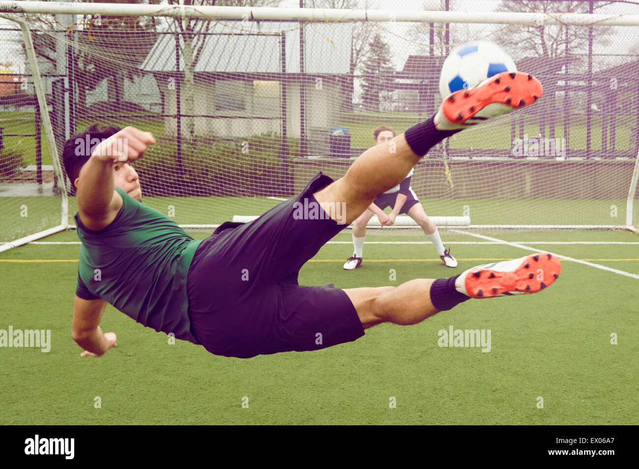 Young male soccer player kicking ball toward goal - Stock Image