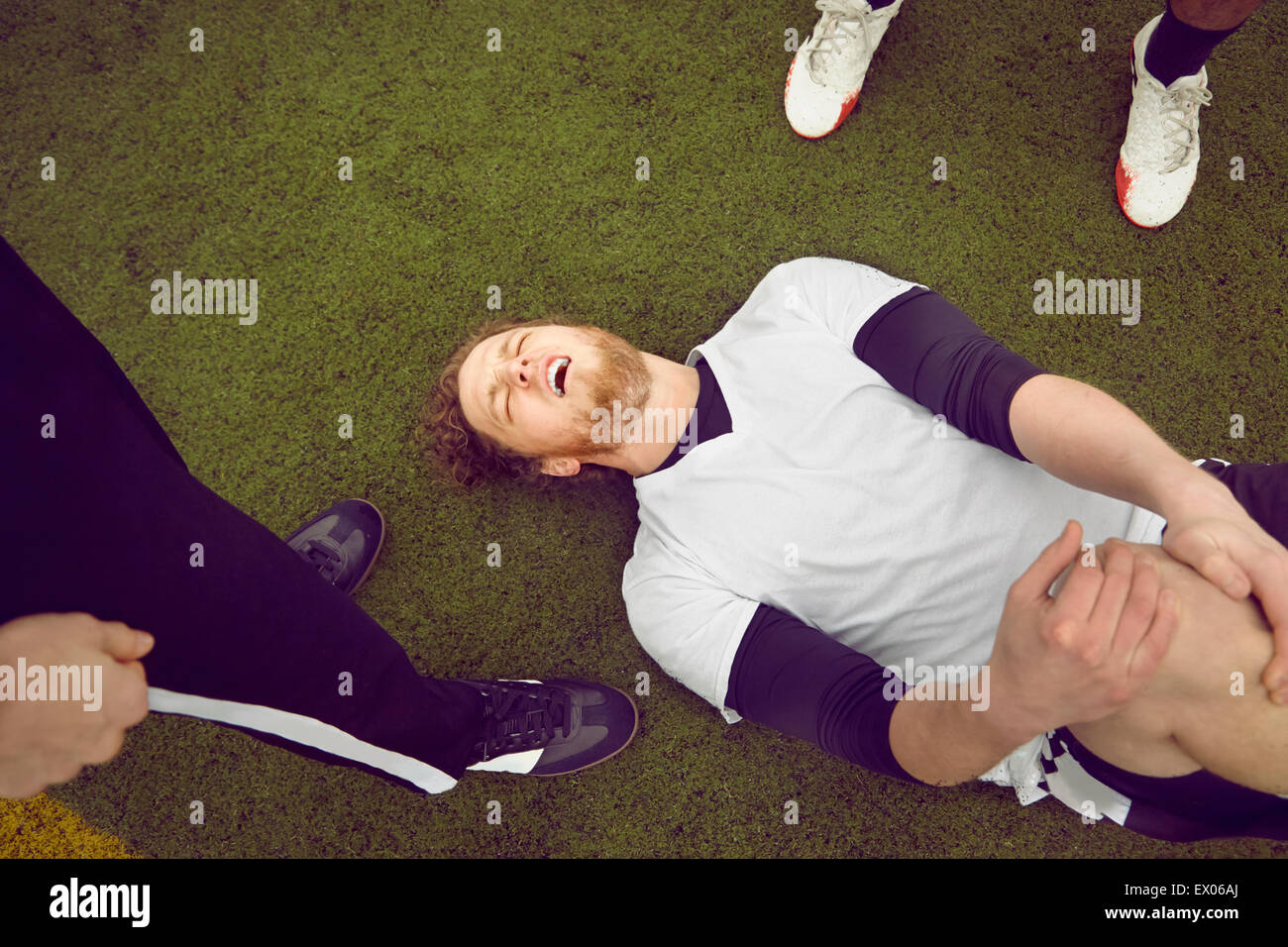 Injured male soccer player on soccer pitch - Stock Image