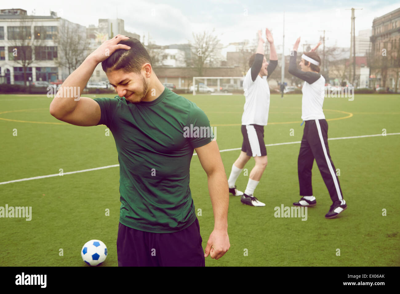 Disappointed male soccer player with hand in hair on soccer pitch - Stock Image