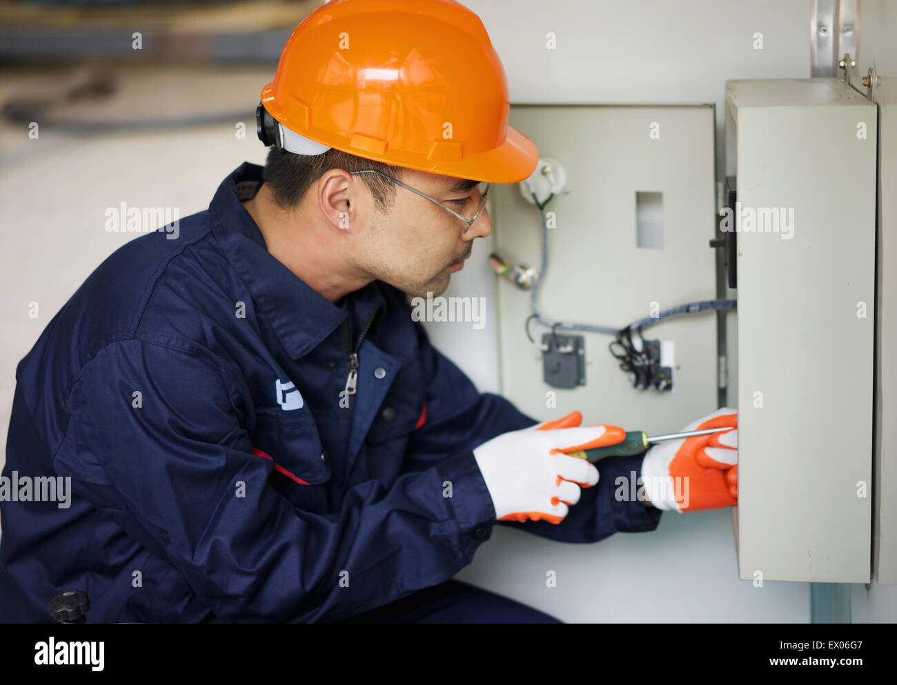 worker working on fuse box in crane manufacturing facility, china - stock  image