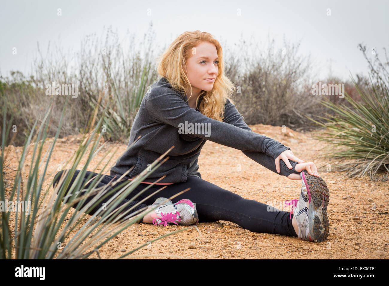 Young female runner stretching to touch toes - Stock Image