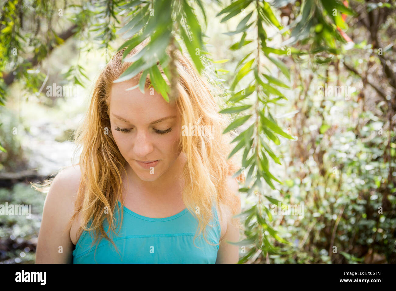 Portrait of young female hiker on riverside - Stock Image