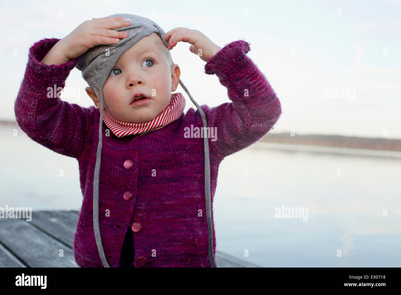 f17bad41 Baby girl on lake pier trying to put on hat Stock Photo: 84828052 ...