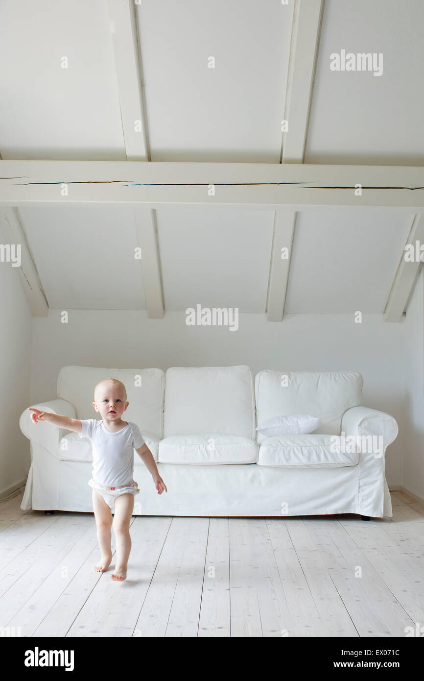 Portrait of baby girl toddling and pointing in living room - Stock Image
