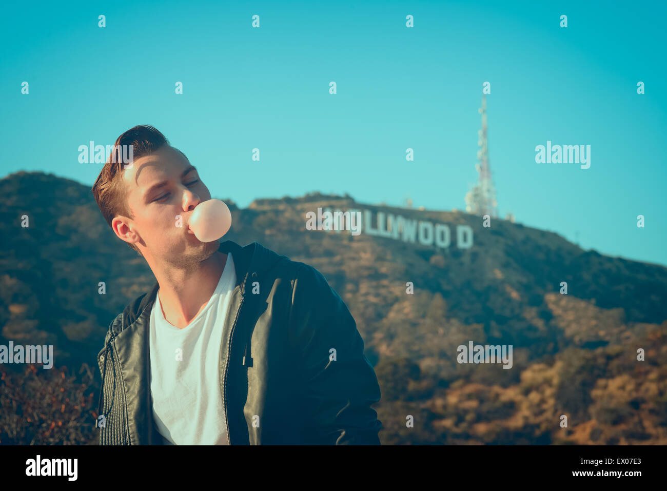 A Happy Man Blowing Bubble Posing Outdoor With The Hollywood Sign In Background At Sunset Mens Vintage Fashion Editorial Concept