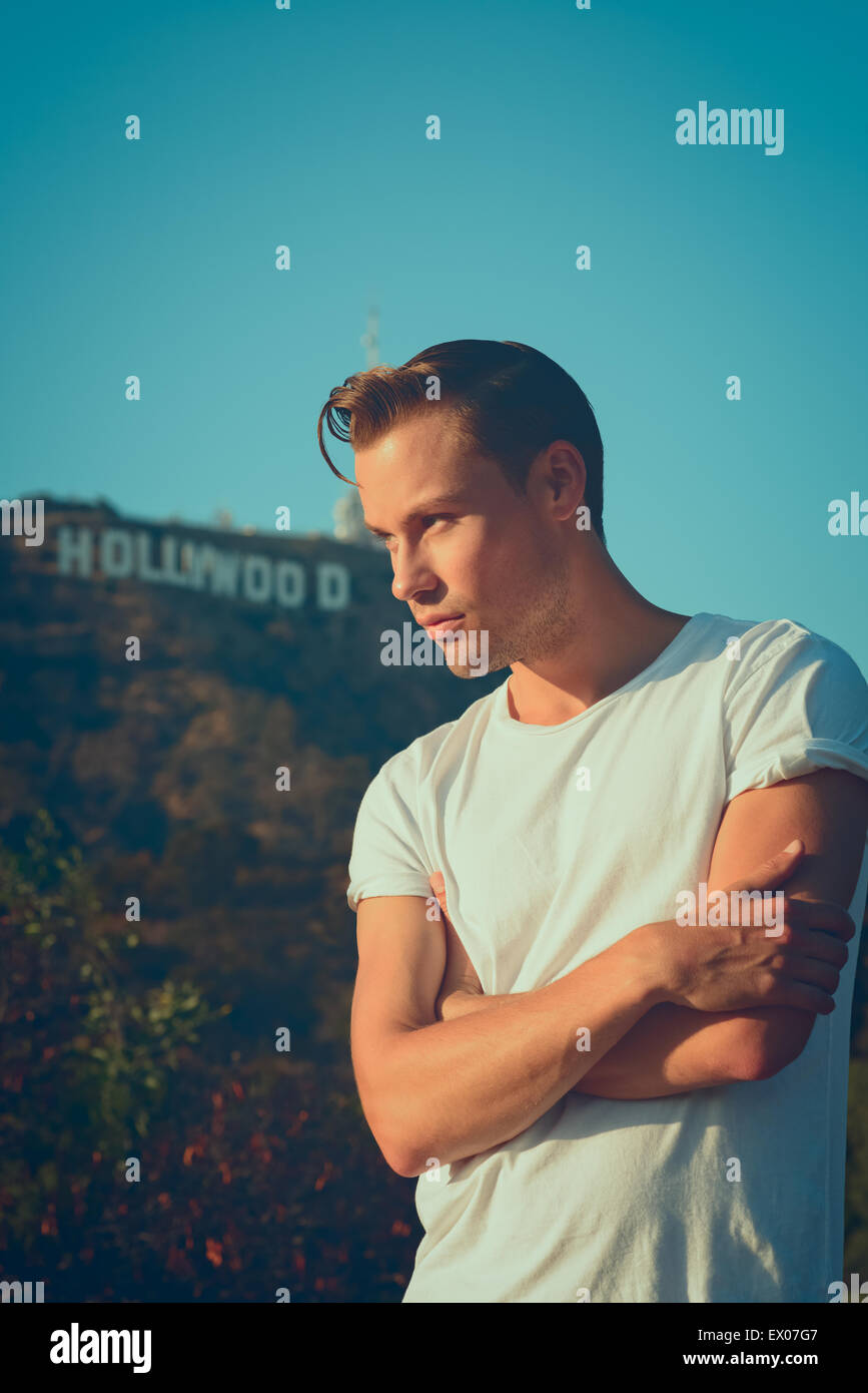 A Vintage Portrait Of Young Man Male Model Posing In White T Shirt With The Hollywood Sign Background 50s Retro Fashion Concept
