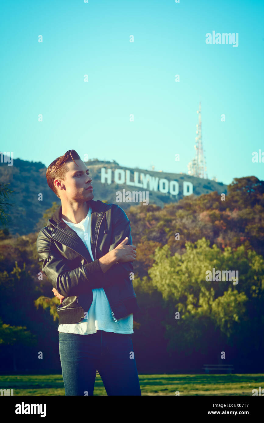 A Vintage Portrait Of Young Man Wearing Black Leather Jacket And Blue Jeans With The Hollywood Sign In Background Fashion Concept