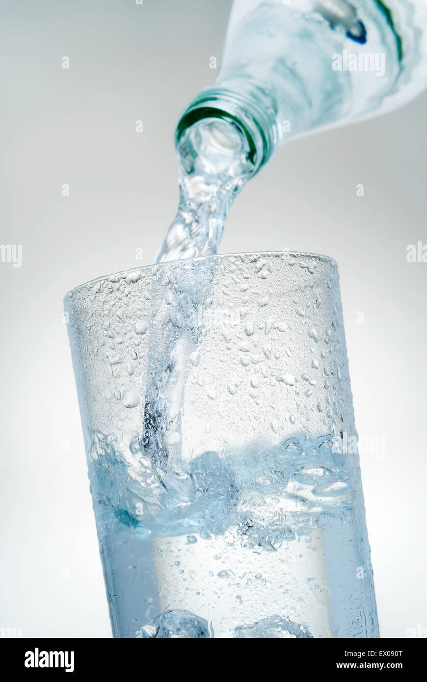 Mineral water is poured into a glass. - Stock Image