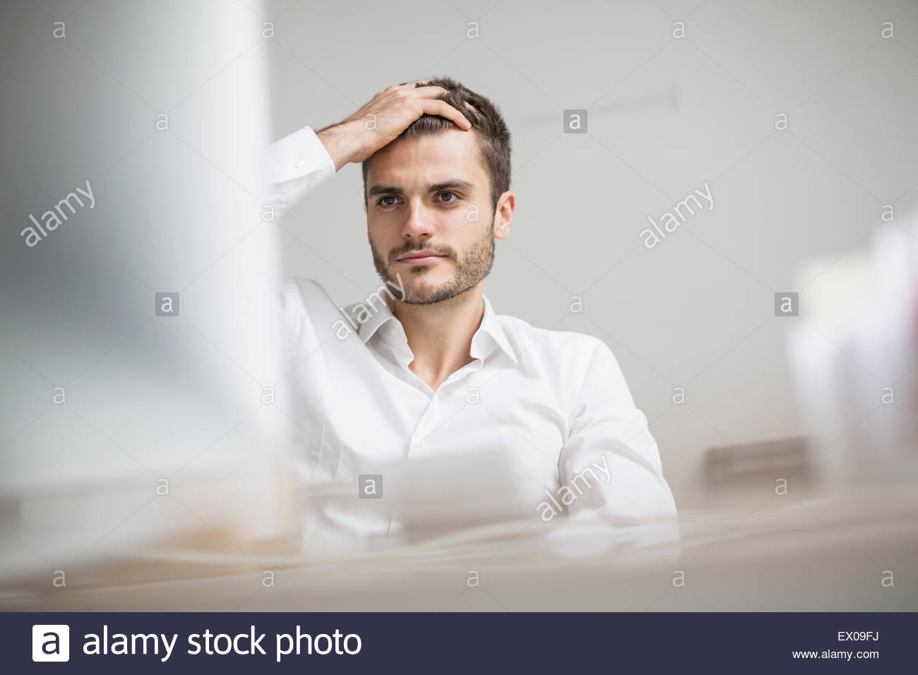 Young businessman at desk looking at personal computer - Stock Image