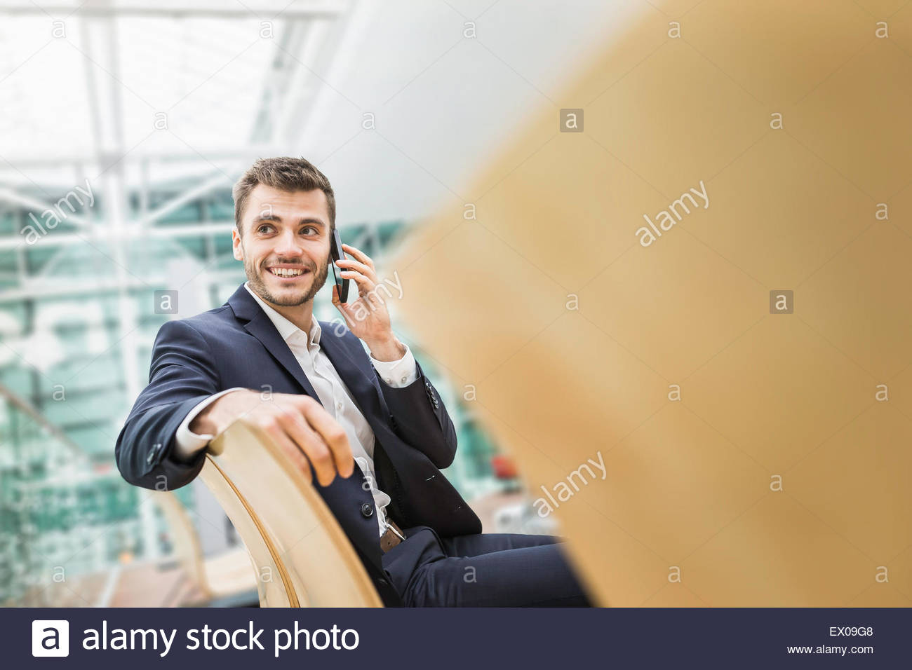 Young businessman in airport departure lounge chatting on smartphone - Stock Image