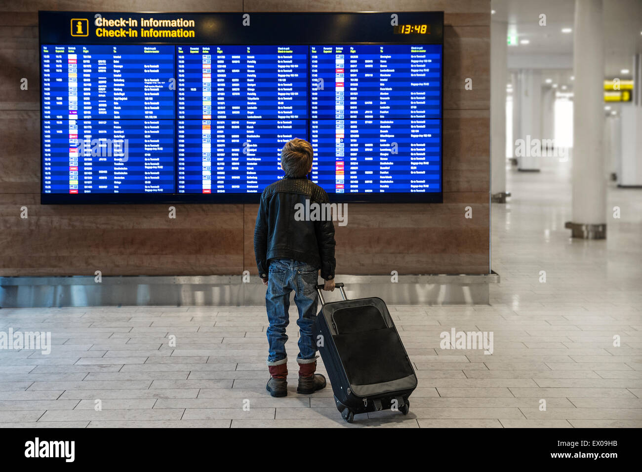 Rear view of boy with wheeled suitcase looking at airport departure board - Stock Image