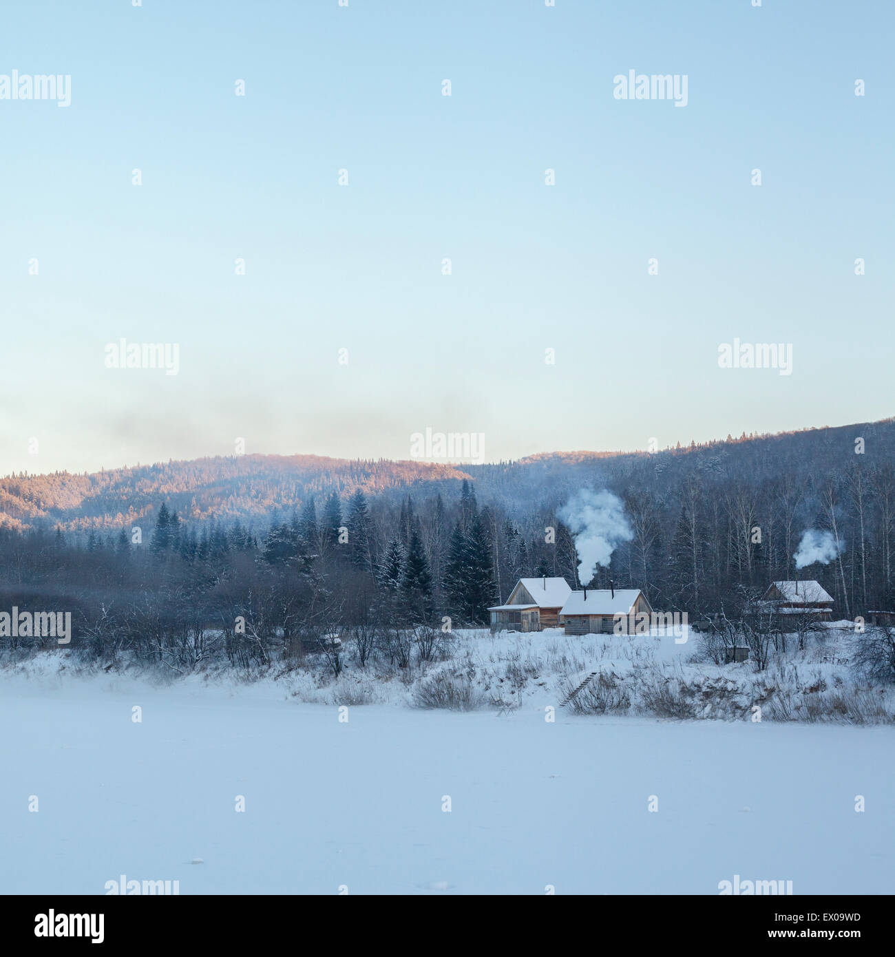 View of distant houses and forest in snow covered landscape, Sarsy village, Sverdlovsk Oblast, Russia - Stock Image