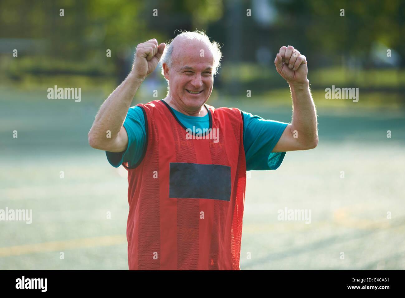 Senior man wearing sports bib cheering - Stock Image