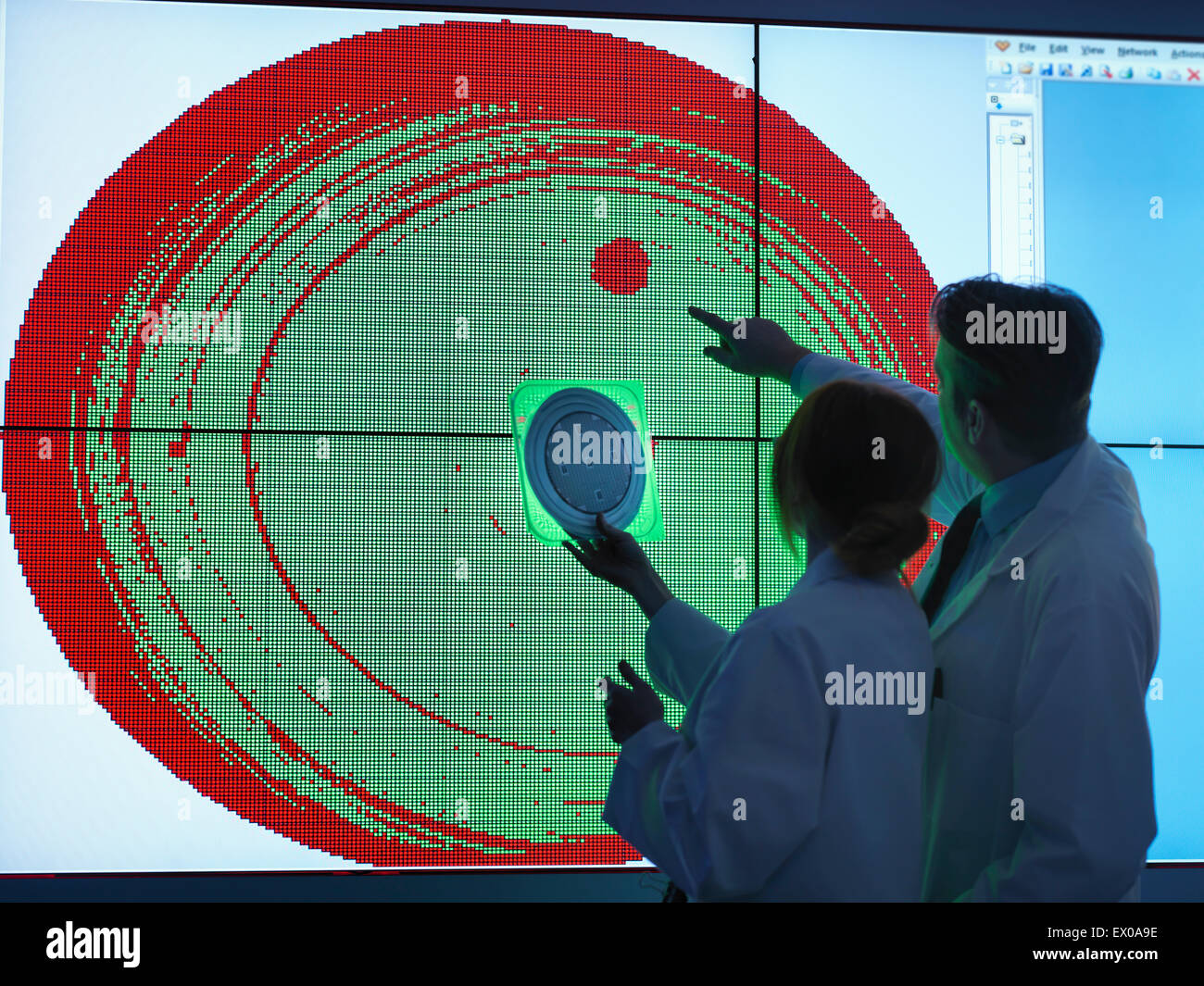 Scientists studying graphical display of silicon wafer on screens - Stock Image
