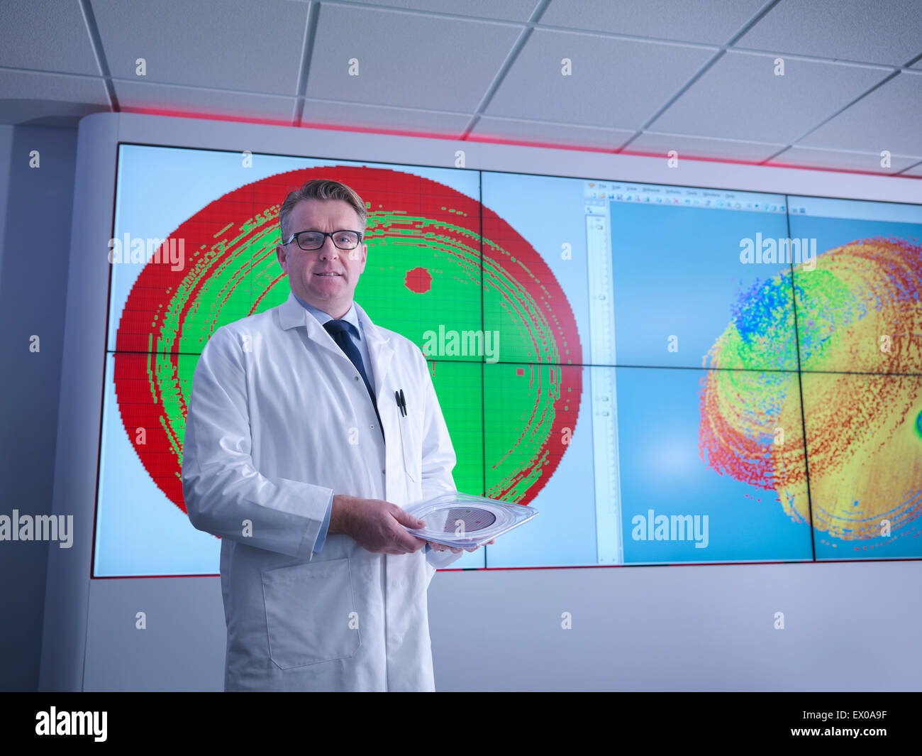 Portrait of scientist in front of graphical display of silicon wafer on screens - Stock Image