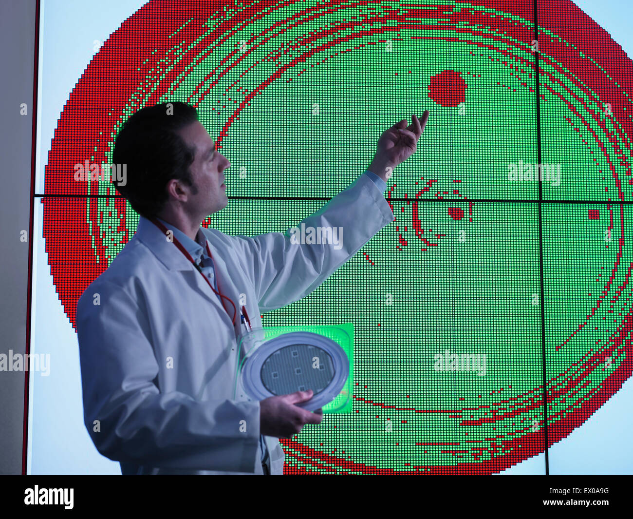Scientist studying graphical display of silicon wafer on screens - Stock Image