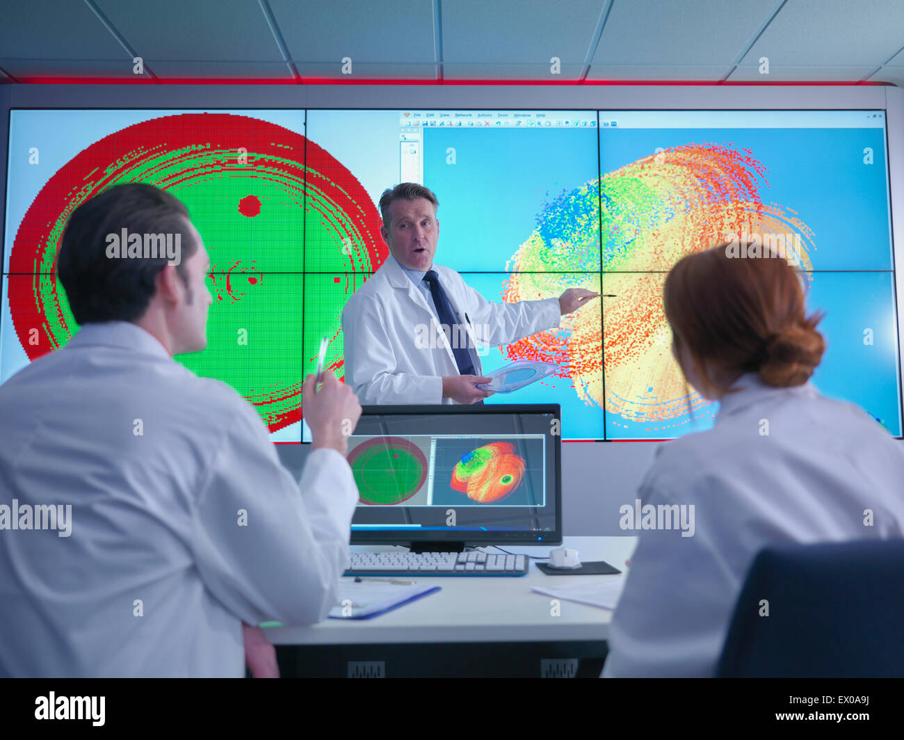 Scientists in meeting in front of graphical display of silicon wafer on screens - Stock Image